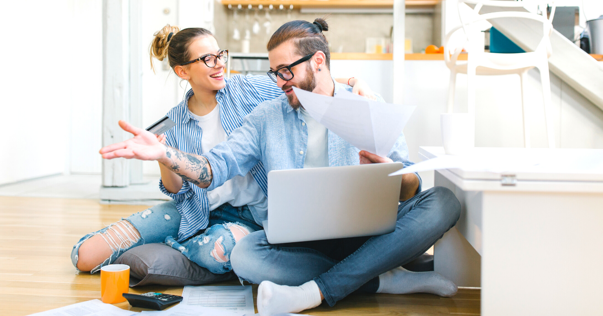 Happy young couple using a credit card and going through home finances