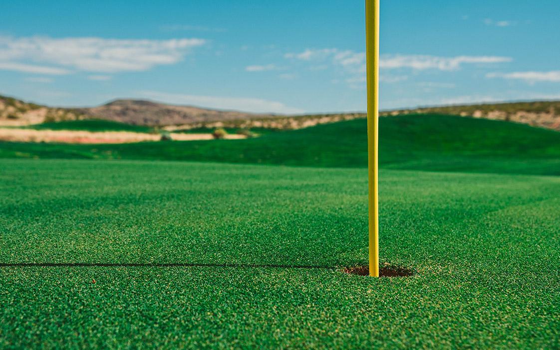 A flag inside a hole at a golf course