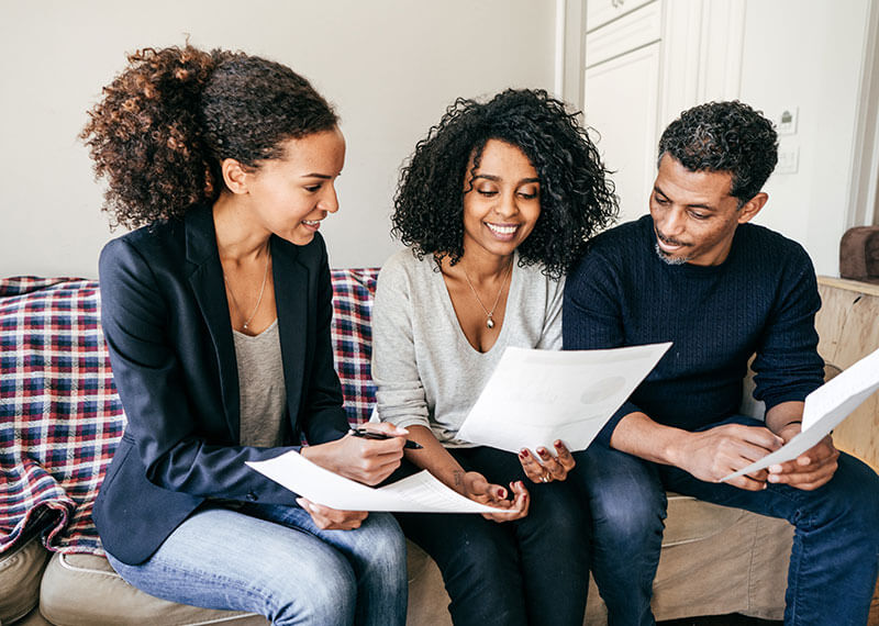 Loan officer and couple reviewing paperwork