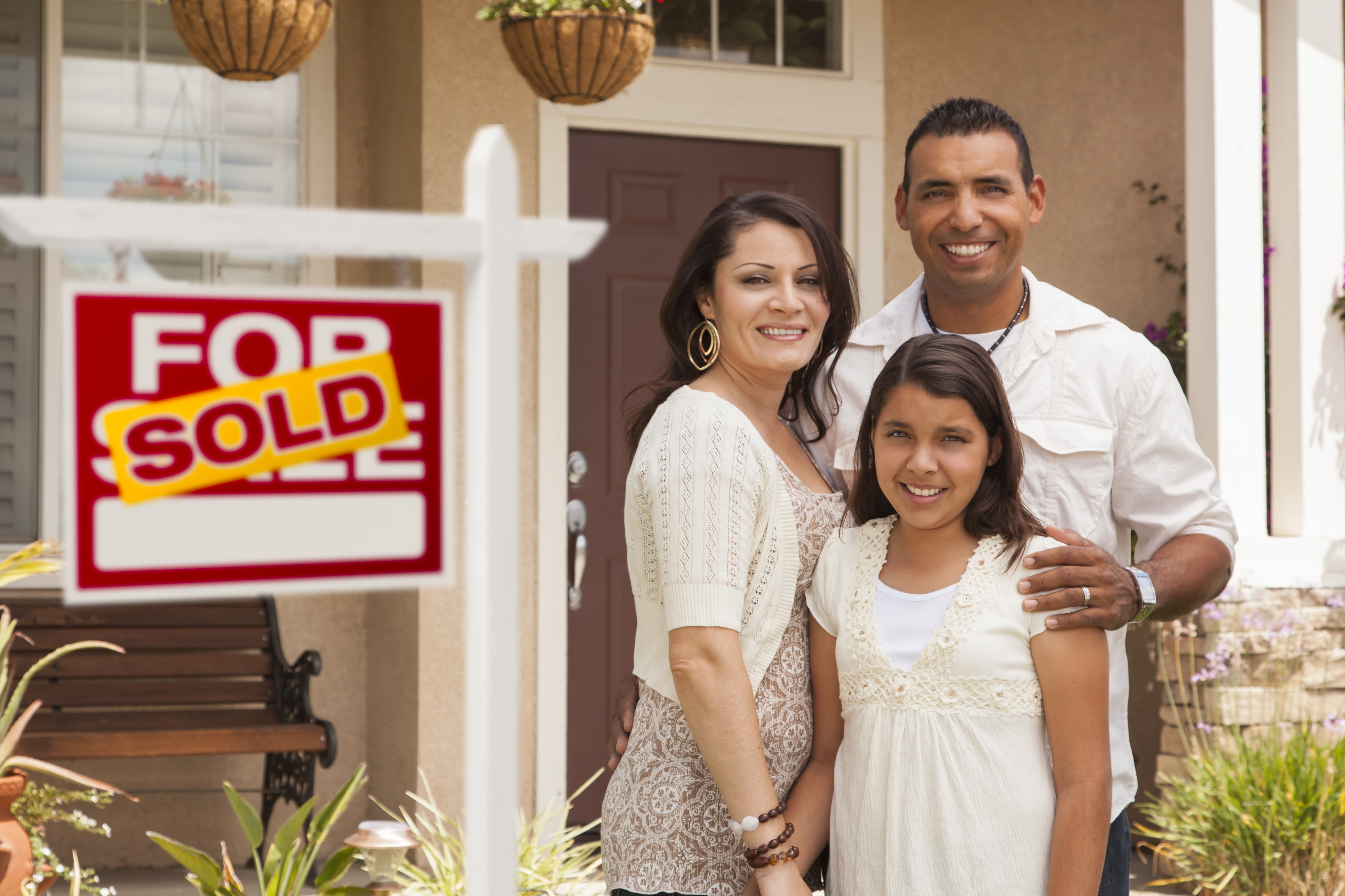 A family of three standing in front of a house with a sold sign