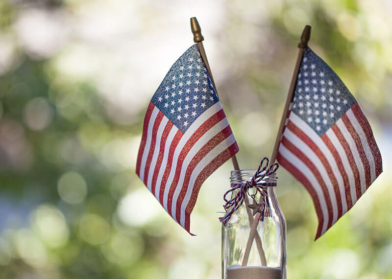 Two American Flags sitting in a mason jar outside