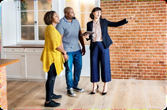 A realtor showing a couple the inside of a home