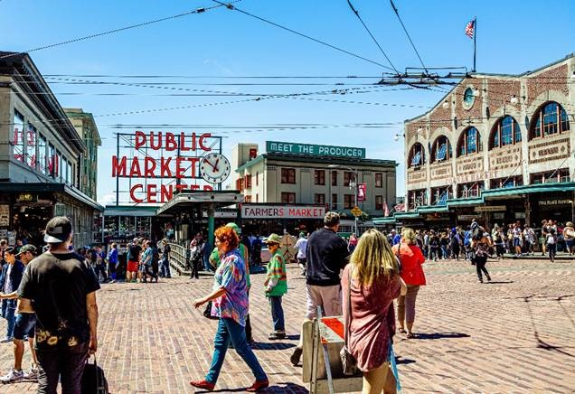 The Public Market Center sign with people walking around in Seattle Washington