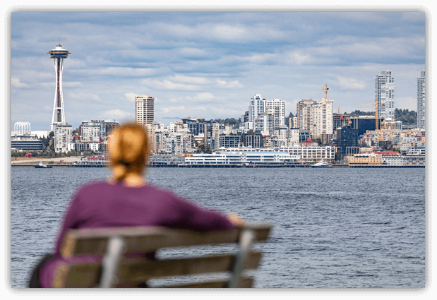 Woman on a bench looking at Seattle skyline