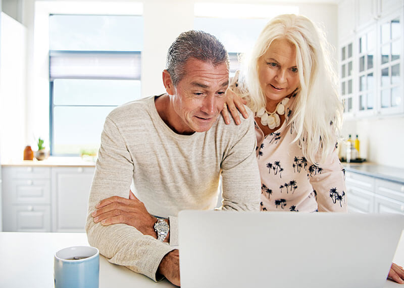 An eldery couple looking at a computer screen in their kitchen