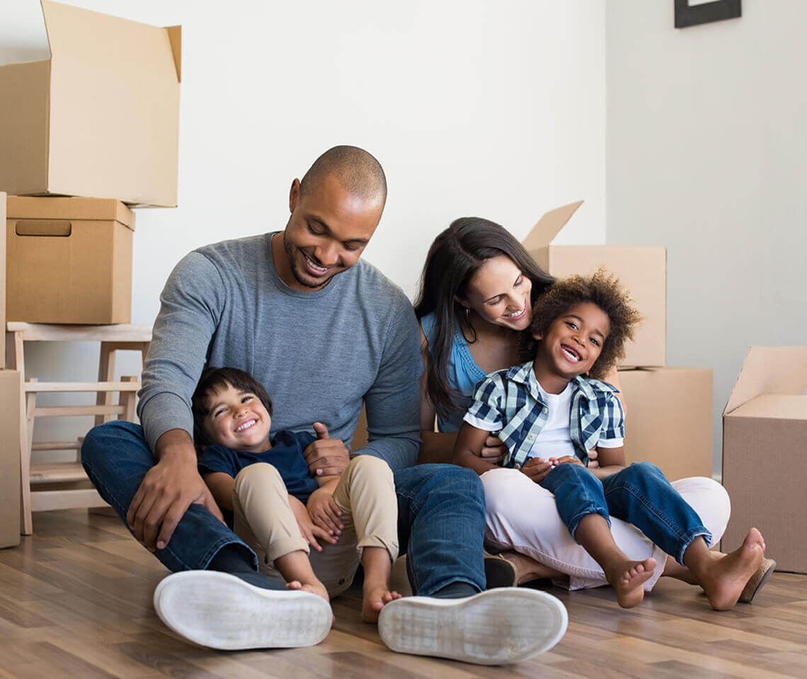Family of 4 sitting on wood floor laughing with boxes surrounding them